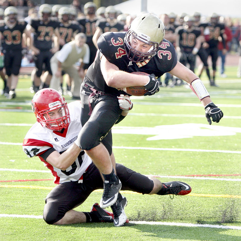 Conor McCann of Scarborough brings down Nick Kenney of Thornton Academy at the 1-yard line in the fourth quarter Saturday in Saco. The Trojans won, 28-14.