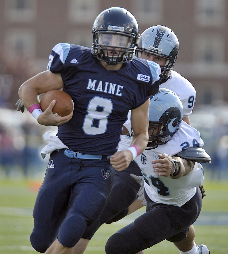 University of Maine quarterback Warren Smith scrambles away from Rhode Island's Dave Zocco (24) and James Timmins during Saturday's game at Orono. Smith threw three touchdown passes to help the Black Bears build a 27-7 lead on the way to a 27-21 Colonial Athletic Association victory.