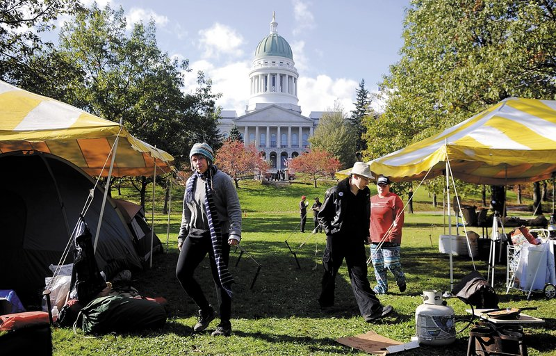 """Occupy Augusta protesters walk Sunday between canopies covering tents at Capitol Park. The group plans to distribute statements on its key issues to passers-by, focusing on """"those institutions that are keeping us in poverty,"""" a spokesman said."""