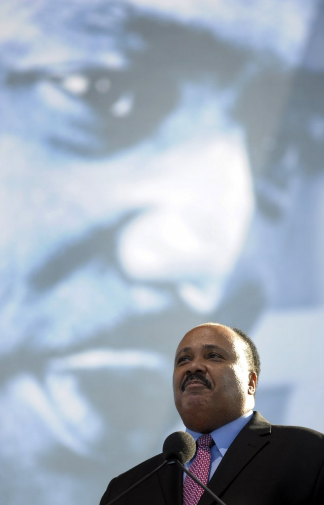 Standing beneath an image of Martin Luther King Jr., Martin Luther King III speaks at the dedication of his father's memorial in Washington on Sunday.