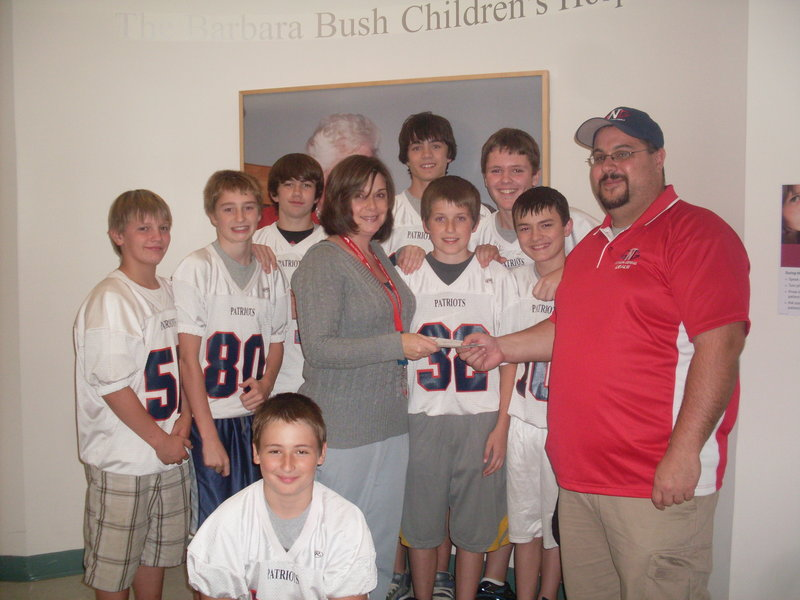 Gray-New Gloucester Middle School football coach Justin Bisson, right, and his team visited the Barbara Bush Children's Hospital on Friday to meet with patients and present a donation of $2,100 raised by the team.