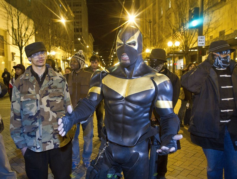 Self-described superhero Phoenix Jones meets with protesters at a Seattle park last February during a rally against police brutality. Police arrested Jones, whose real name is Benjamin Fodor, earlier this month and are investigating whether he assaulted several people with pepper spray while trying to break up an alleged fight.
