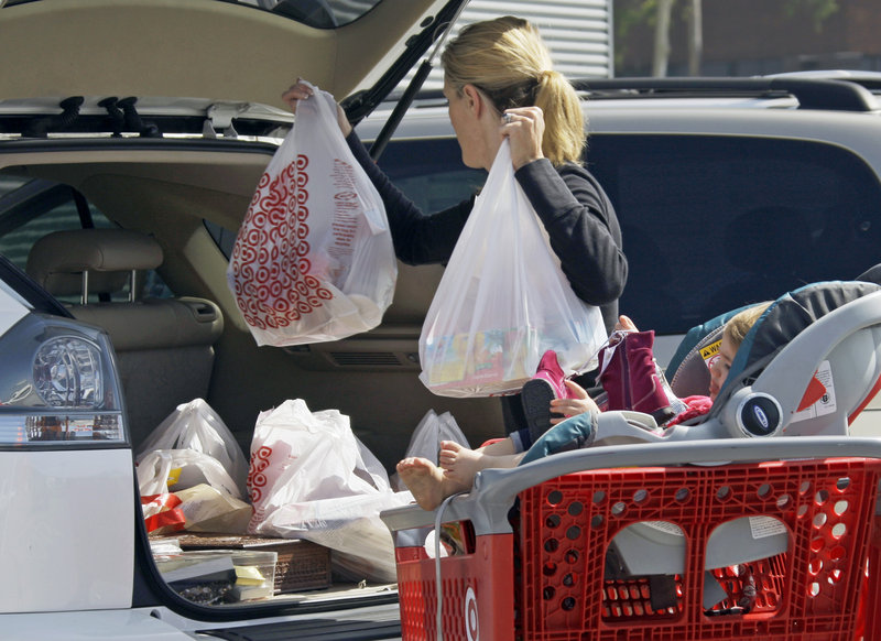 """A woman loads her car with purchases from a Target in Culver City, Calif. ShopperTrak says Web-savvy women are doing more """"surgical shopping"""" and less browsing in stores."""