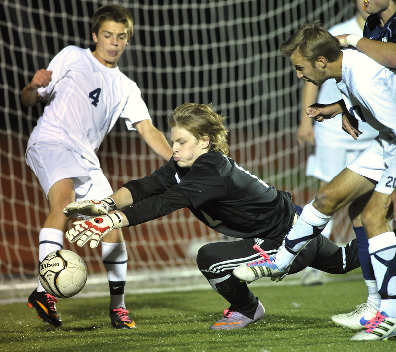 John Ewing/Staff Photographer Yarmouth keeper Andrew Fochler dives for a loose ball as defender David Murphy, left, backs him up. Fochler made the start in place of Christopher Knaub, who was injured. Fochler's stepbrother, Nathan Diffin, is York's keeper.