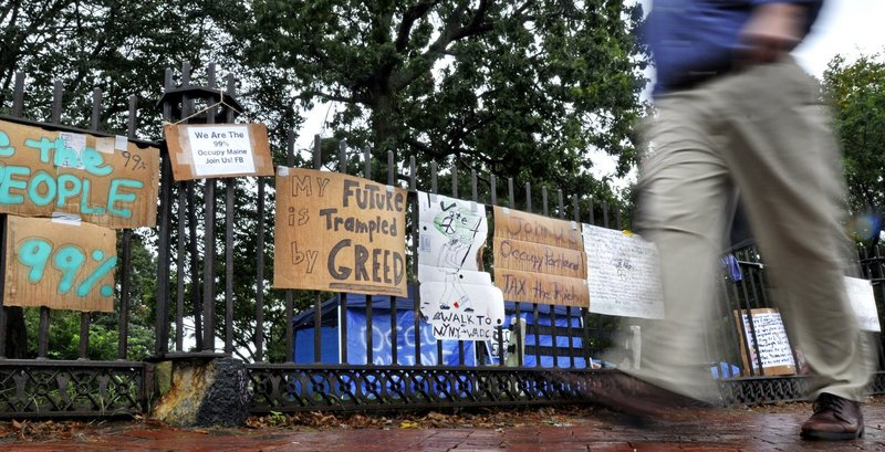 A pedestrian on Oct. 4 walks past signs placed on the fence of Lincoln Park in Portland by the group Occupy Maine.
