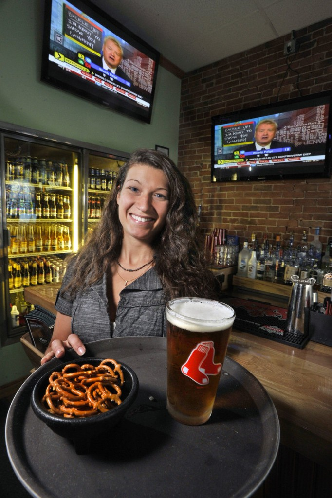 Thatcher's bartender Tonia Pelletier serves a draft beer and snack of pretzels.