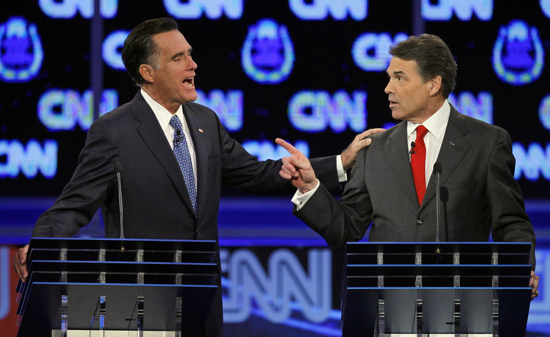 Former Massachusetts Gov. Mitt Romney, left, and Texas Gov. Rick Perry confront each other during the Republican presidential debate Tuesday in Las Vegas.