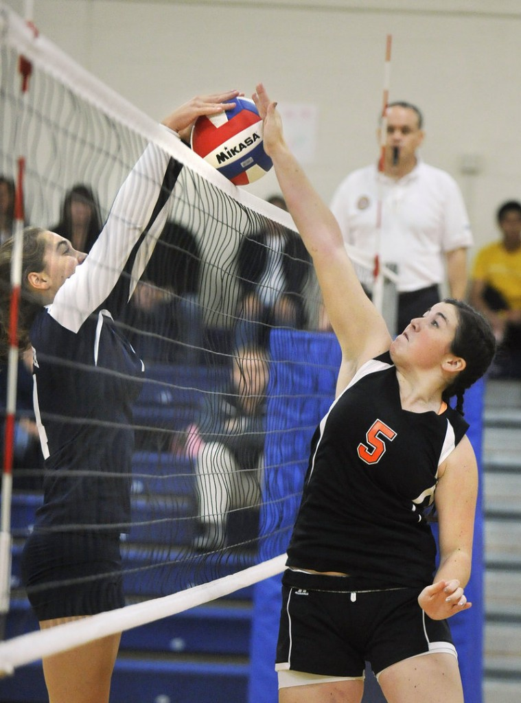 Gina Robertson of Yarmouth, left, attempts to block a shot by Jodie Wood of Machias during their Class B volleyball quarterfinal Wednesday. Yarmouth advanced with a straight-set victory at home.
