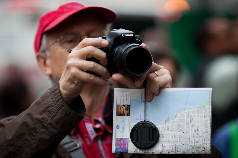 A spectator takes a photograph of the Occupy Wall Street encampment in New York's Zuccotti Park, as the movement continues into its second month.