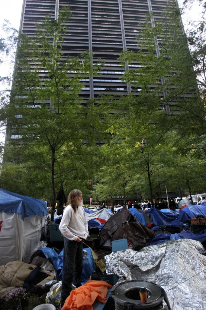 An Occupy Wall Street protester in Zuccotti Park stands amid tarps and sleeping bags Thursday in the shadow of a building owned by Brookfield Properties. Zuccotti Park is owned by a wealthy real estate magnate who has properties worldwide and millions of dollars on hand – precisely the sort of corporation the protesters have been shouting about.
