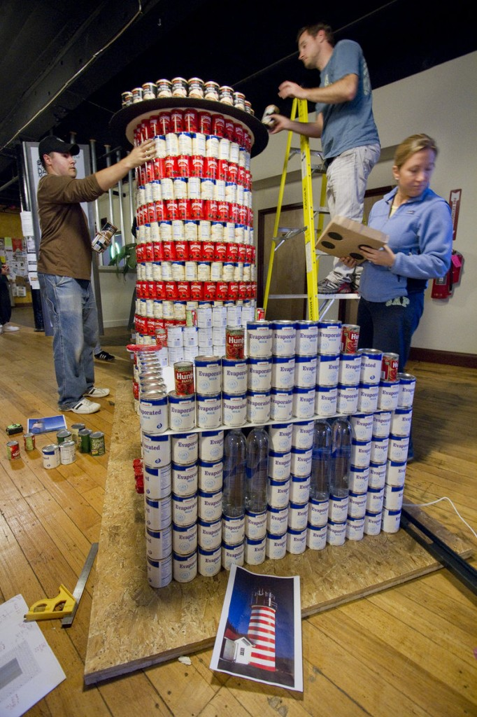 A team from Oak Point Associates of Biddeford builds a replica of West Quoddy Head Light out of cans during a Canstruction competition in Biddeford on Saturday. The team, working in the North Dam Mill, was one of five competing in three downtown locations. Food, provided by participants, will be donated to Friends of Community Action's pantry.