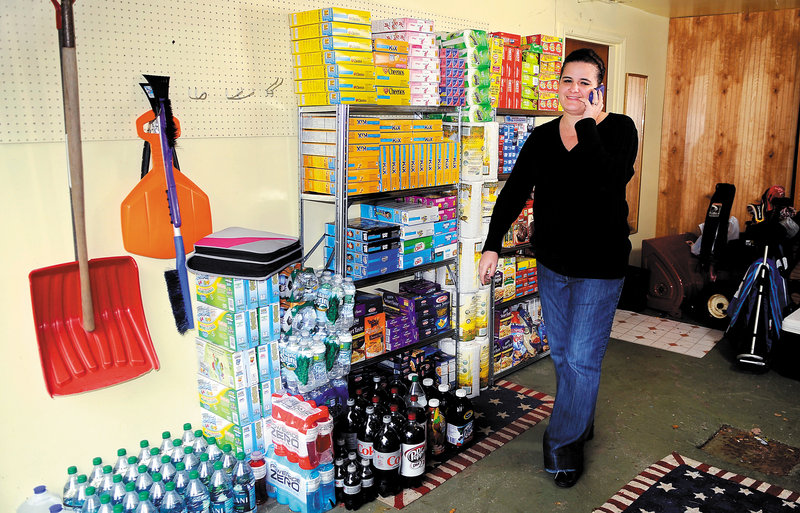 Amanda Fontaine takes a call Thursday in the garage of her Augusta home where she stores groceries. She and her friend Jen Barrows of Manchester call themselves the Coupon Chicks of Maine and have a Facebook page about local deals.