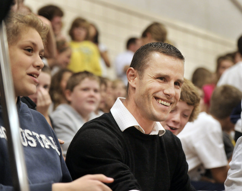 Morgan Cuthbert grins as he is announced as winner of a Milken Educator Award at Monday's surprise assembly.