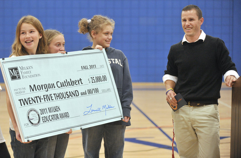 Middle school students hold a check made out to Cuthbert after his award was announced Monday.