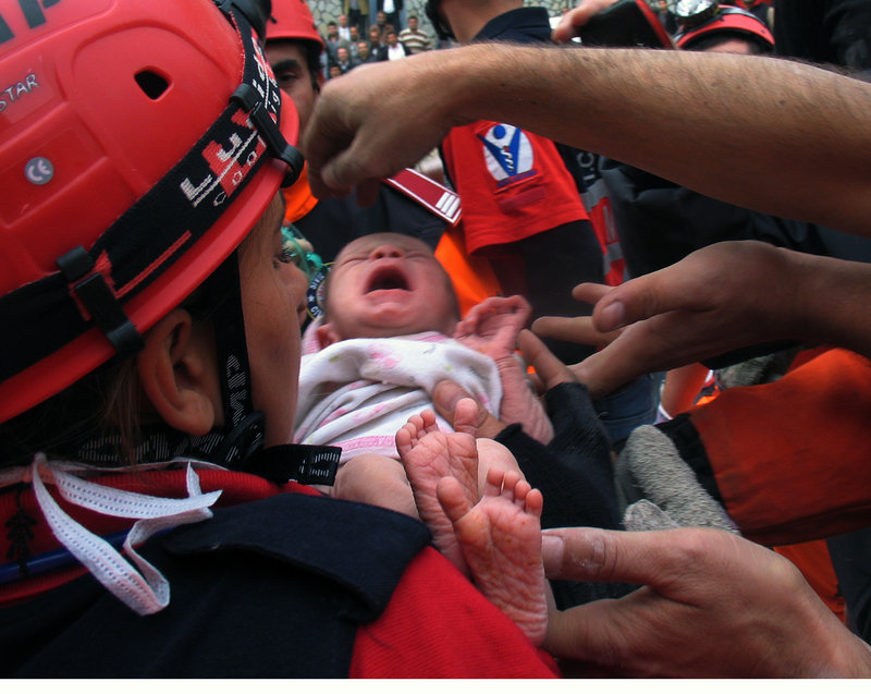 Turkish rescuers carry 2-week-old Azra Karaduman after she was removed Tuesday from the rubble of a collapsed building in eastern Turkey two days after a 7.2-magnitude earthquake. The infant was declared healthy after being flown to a hospital.