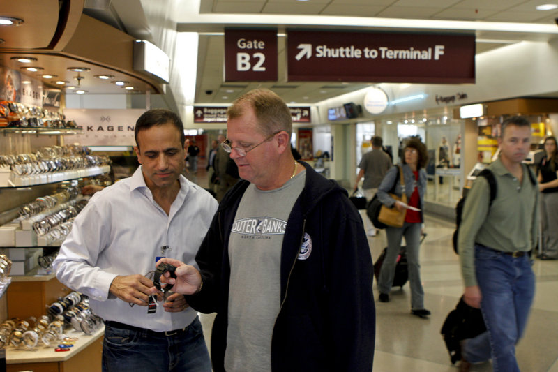 """Ben Cohen shows a watch to traveler Shawn McElroy. """"I sell image,"""" Cohen says. """"I don't sell time."""""""