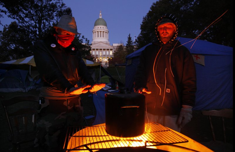 Occupy Maine protesters in Augusta warm their hands while brewing coffee on a fire pit at their encampment across from the State House early Friday morning. About 30 protesters in Augusta and dozens more in Portland camped out in near-freezing temperatures as they continued their protests against Wall Street excesses. The temperatures are likely to test their mettle again tonight as lows plummet to the mid-20s.