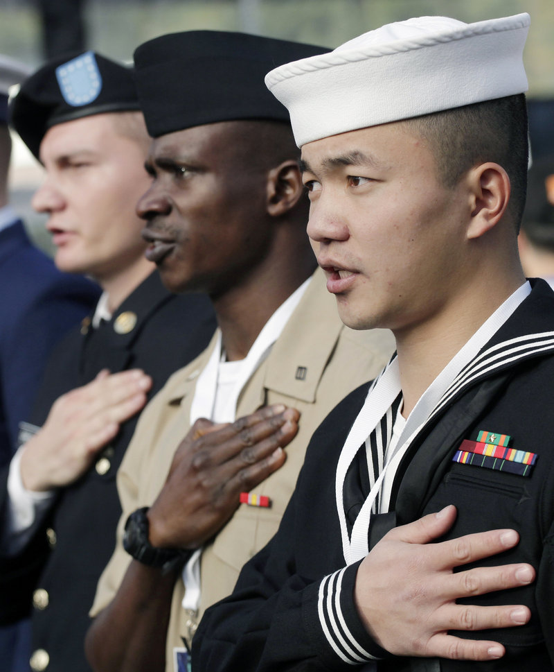Zuyu Nu, right, who was born in China and serves in the U.S. Navy, takes the oath of citizenship, with 124 others from 46 countries, during a naturalization ceremony at the Statue of Liberty on Friday in New York.
