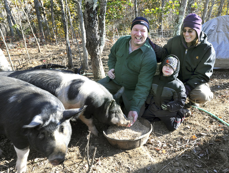 Glen and Rachel Powers and their son Nestor, 4, feed their remaining pigs at their home in Windsor. Chickens, turkeys and pigs are among their donations to the Augusta Food Pantry.
