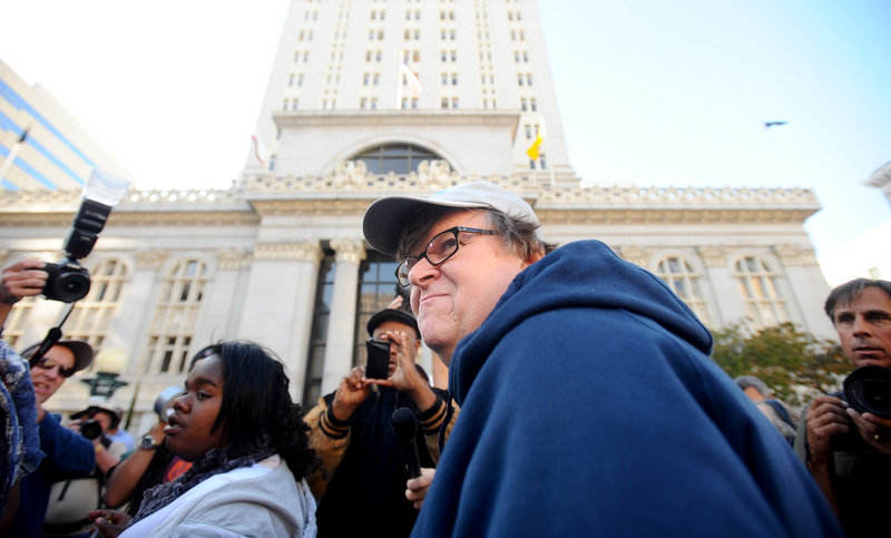Filmmaker Michael Moore visits with the Occupy Oakland protesters outside City Hall in Oakland, Calif., on Friday. A severe injury to Iraq war veteran Scott Olsen – caused by police, protesters say – has attracted growing attention to this city's participants in the movement.