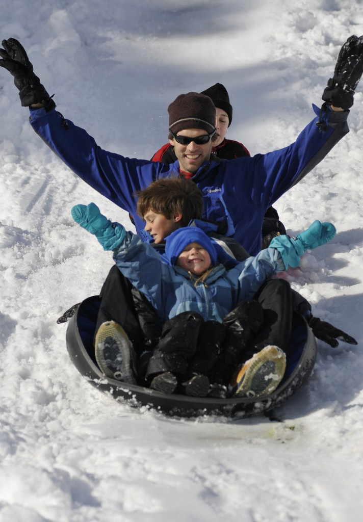 Jeff Hanselmann makes the best of the weekend snowfall at Gowen Park in Sanford with his daughter Caiti, 5, son Stephen, 8, and, at rear, friend Peter Nolin, 10, all of Springvale.