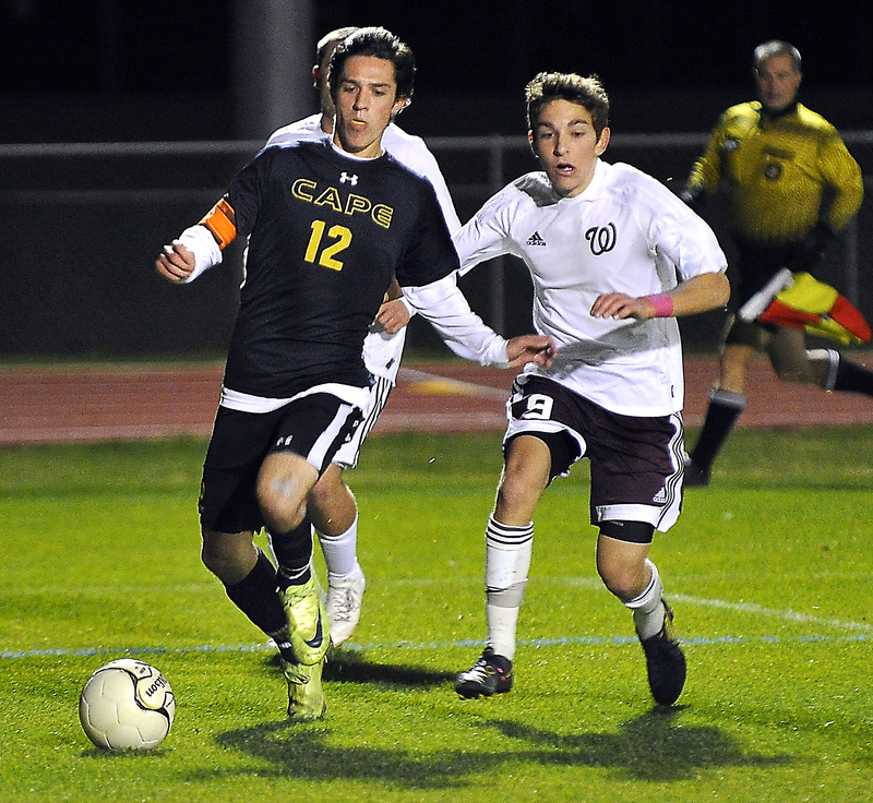 Tim Lavallee of Cape Elizabeth drives toward the goal as Windham's Dalton Mauro gives chase.