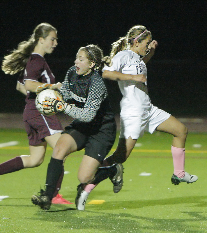 Greely keeper Caton Beaulieu hangs onto the ball as Thornton Academy's Jaime Durie, right, charges by during a Western Class A quarterfinal Wednesday in Saco. Durie had two goals and an assist to lead the Trojans to a 3-2 victory.