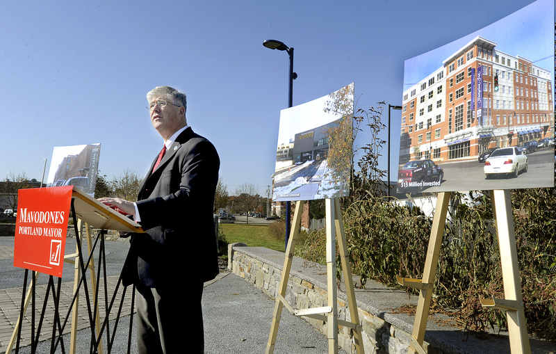 City Councilor and incumbent mayor Nicholas Mavodones speaks along the Bayside Trail in Portland Wednesday. Photos of recent development projects by law firm Pierce Atwood, left, the Portland International Jetport, center, and Hampton Inn are on display behind him.