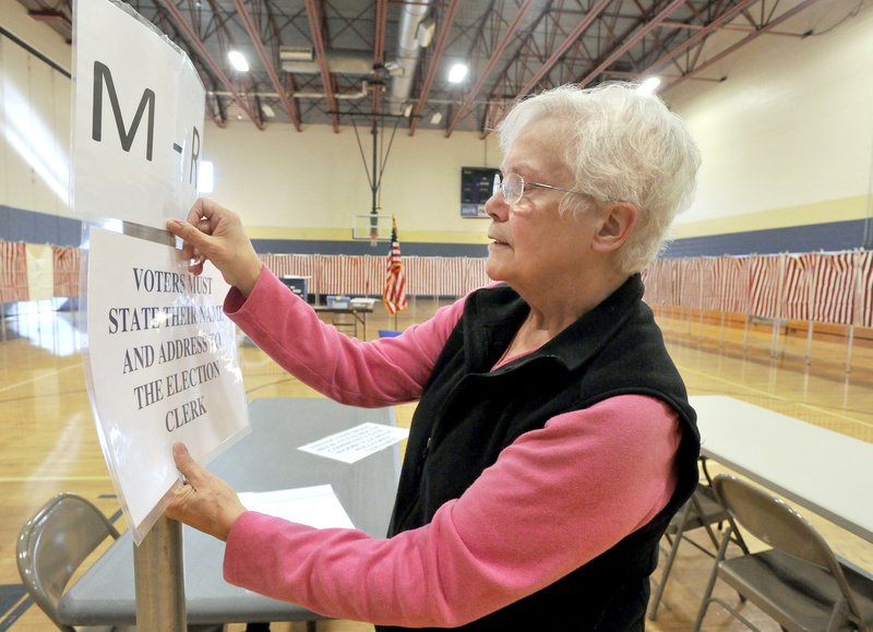 Falmouth deputy warden Sandra Davis tapes up instructions for voters Monday as she readies the polling place at Falmouth High School for today's elections.