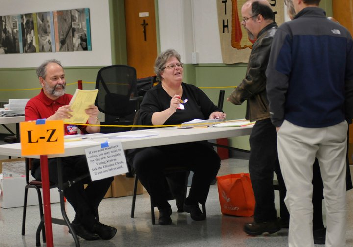 Tim Whitney and Susan Garfield of Portland, election clerks at St. Pius Church polling place in Portland, check in voters today.
