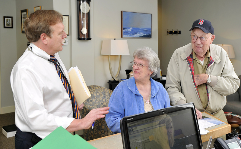 Dr. Philip Frederick chats informally with patients Gladys and Bradley Curtis of Freeport at his office in Yarmouth as they make their appointments for the next visit. Frederick is the first Maine physician to join MDVIP, a Florida-based company with a network of about 500 concierge medical practices.