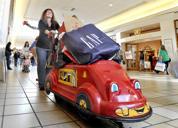 Carrie Campbell from Skowhegan pushes a loaded kiddie cart as she navigates among Black Friday shoppers at the Maine Mall in South Portland today.