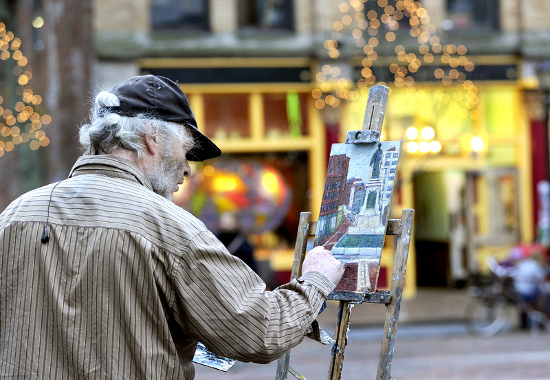 Portland artist Dennis Hare enjoys Monday's balmy 60-degree weather to paint the scene at Monument Square in Portland. Above-average temperatures are forecast through midweek, with rain expected tonight through Wednesday morning.