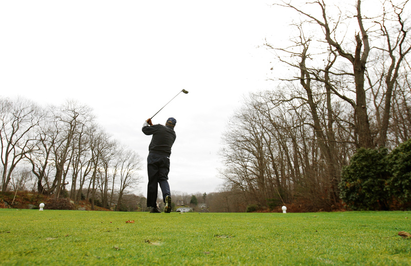 "Taking advantage of unseasonably warm temperatures, Dick Carson tees off the first hole at Purpoodock Club in Cape Elizabeth on Tuesday. ""If the greens are available, (golfers) are going to be out there playing,"" said clubhouse manager Robyn Violette."