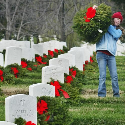 A volunteer helps place Christmas wreaths on the graves at Arlington National Cemetery in this 2004 photo.