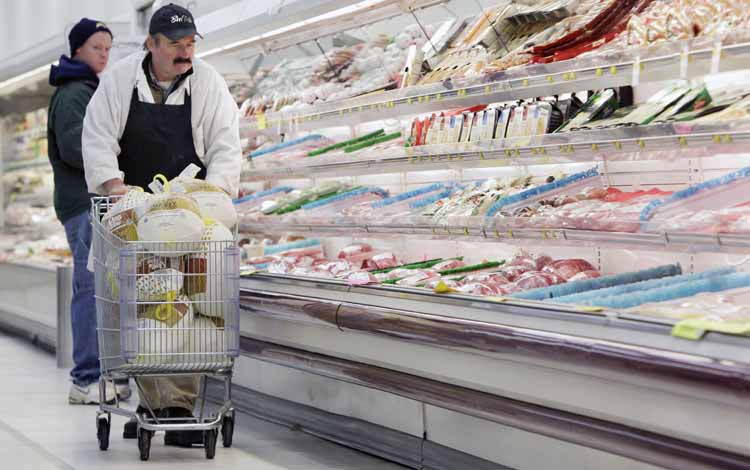 Dennis Sheehan, meat manager, pushes a shopping cart full of turkeys for stocking at Pixley's Shurfine grocery store in Akron, N.Y., today.