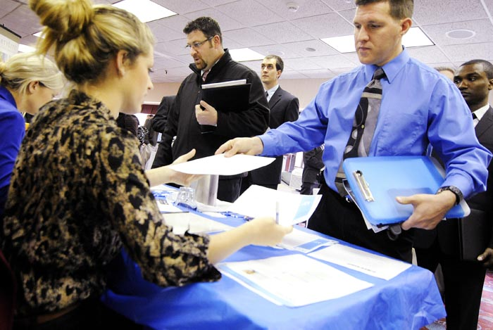 Clarence Turner of Little Canada, Minn., hands in his resume at the Minneapolis Career Fair held in Bloomington, Minn., recently.