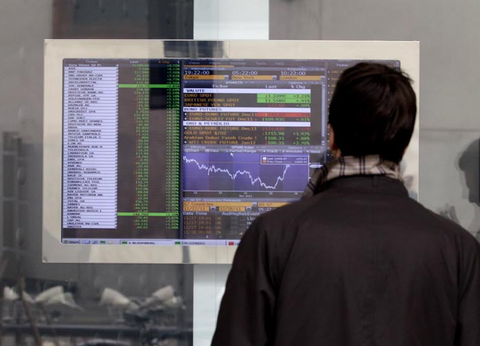 A man checks stock indexes on a screen of a bank in Milan, Italy, today. For the second time in as many market days, Italy paid sharply higher borrowing rates in an auction today, as investors continued to pressure the eurozone's third largest economy to come up with reforms urgently.