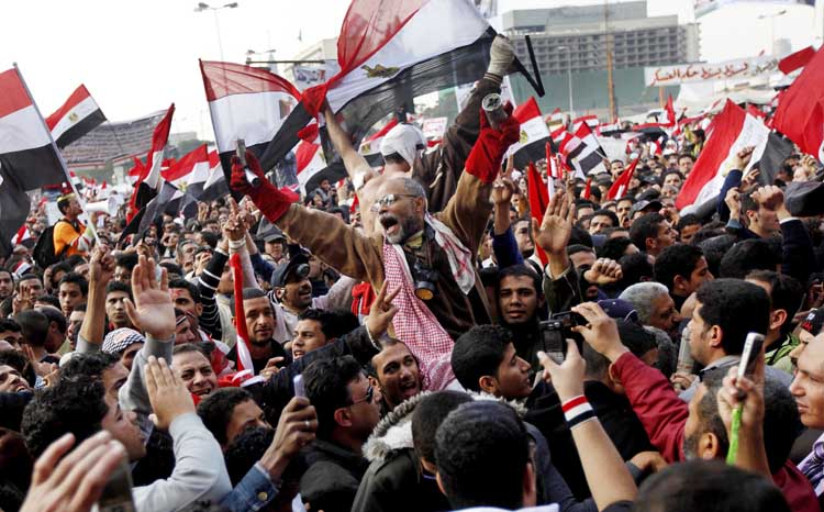 Protesters, including a man holding tear gas cannisters, chant slogans and wave national flags during a rally in Tahrir Square in Cairo today. Tens of thousands of protesters chanting,