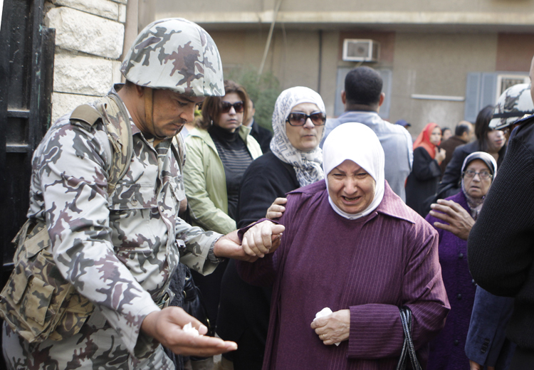 An Egyptian woman is helped by a soldier as she enters a polling center in Cairo today.Voting began today in Egypt's first parliamentary elections since longtime authoritarian leader Hosni Mubarak was ousted in a popular uprising nine months ago.