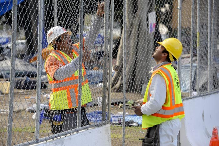 Public works employees erect a fence around Los Angeles City Hall park today.
