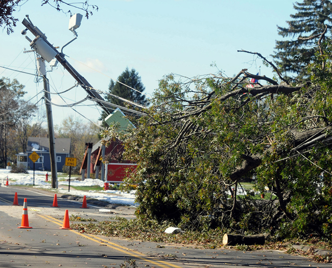 A snapped utility pole leans over the road today in Enfield, Conn., six days into an epic power outage that still has roughly 300,000 Connecticut residents in the dark.