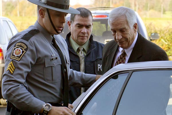 """Former Penn State football defensive coordinator Gerald """"Jerry"""" Sandusky, center, arrives in handcuffs at the office of Centre County Magisterial District Judge Leslie A. Dutchcot while being escorted by Pennsylvania State Police and Attorney General's Office officials on Saturday, Nov. 5, in State College, Pa."""