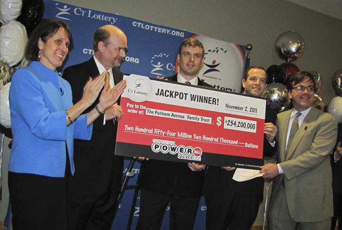 In this photo provided by the Connecticut Lottery in Greenwich, Conn., wealth managers Tim Davidson, second left, Greg Skidmore, center, and Brandon Lacoff, second right, pose Monday with a ceremonial check for $254.2 million. The jackpot was the largest ever won in Connecticut and the 12th biggest in Powerball history.