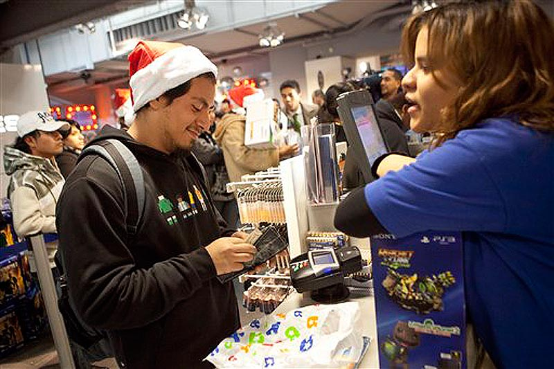 A customer pays for his purchases inside the Toys R Us in Times Square in New York on Thursday, Nov. 24, 2011. The Toys R Us opened at 9PM offering special deals for holiday shoppers. (AP Photo/Andrew Burton)