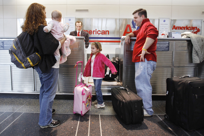 Lori Tempesta, of Falls Church, Va., left, holds her baby Ashlyn Tempesta, next to daughter Elena Tempesta, 3, and husband Anthony Tempesta, as they check in for a flight to Dallas for Thanksgiving, today at Washington's at Ronald Reagan National Airport.