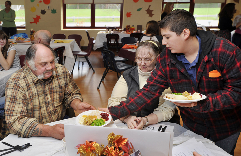 Gordon Chibroski / Staff Photographer. Wednesday, November 16, 2011. Kenneth Hutchins, left, and Karla Taylor of Cape Porpoise are served their meal by Alex Durrell, their grandson, at the Thanksgiving Dinner served by 8th graders to invited senior citizens at Middle School of the Kennebunks.