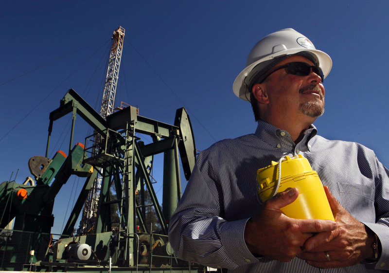 David L. Slater, executive vice president of Signal Hill Petroleum, holds a device that helps the company map out new oil deposits by detecting vibrations.