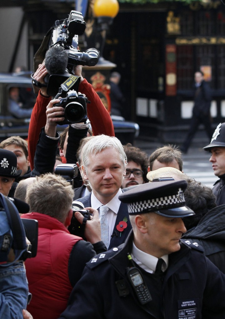 WikiLeaks founder Julian Assange is swarmed by the media in London as he arrives Wednesday for his extradition hearing at the High Court.