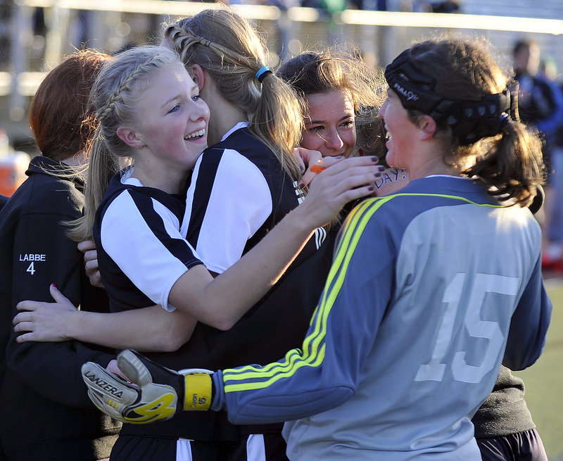 Kayla McLellan, left, is hugged by teammates, including goalkeeper Mary Caron, right, after helping set up the overtime goal by Dayle Jordan that gave St. Dominic of Auburn a 1-0 victory against Waynflete in the Western Class C girls' soccer final Wednesday at Fitzpatrick Stadium.